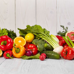an array of colorful fruits and vegetables displayed against a wooden background