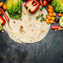 Flat tortillas and various vegetables for burrito making on a table
