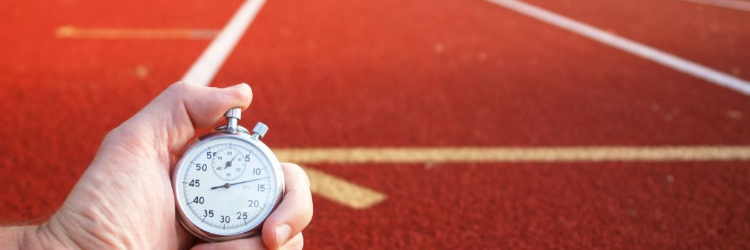 The hand of a coach holding a stop watch in front of a race track