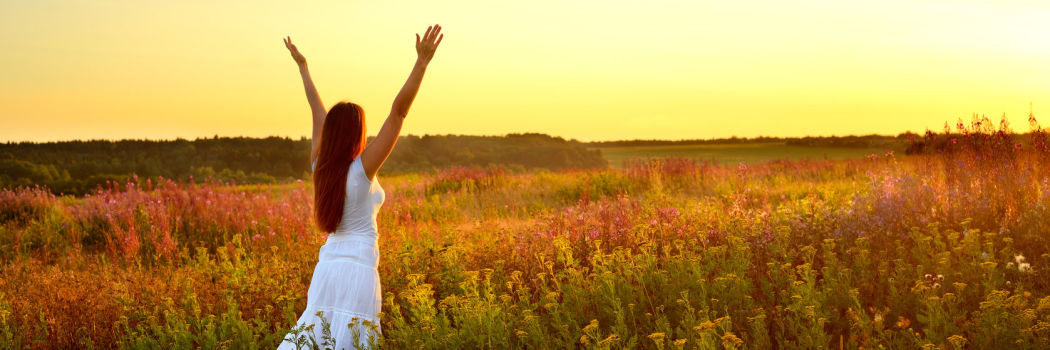 A woman standing in a field with her arms in the air looking at a sunset to illustrate a success concept