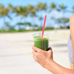 Woman on a beach holding a green smoothie getting into shape for summer