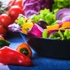 A colorful salad surrounded by fresh pepper and tomato ingredients