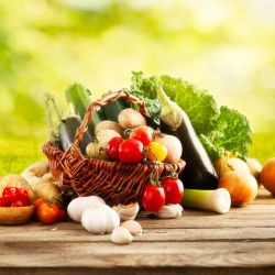 Basket of colorful vegetables on a wooden table outside