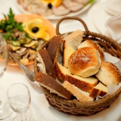 A dinner table at a restaurant with the bread basket in focus