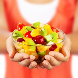 close up of a woman's hands holding out a bowl of colorful fruits