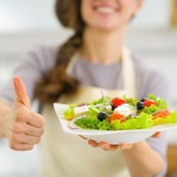 Woman with a thumbs up holding out a salad