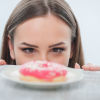 girl looking at unhealthy donut with appetite on a table. Isolated on a white background
