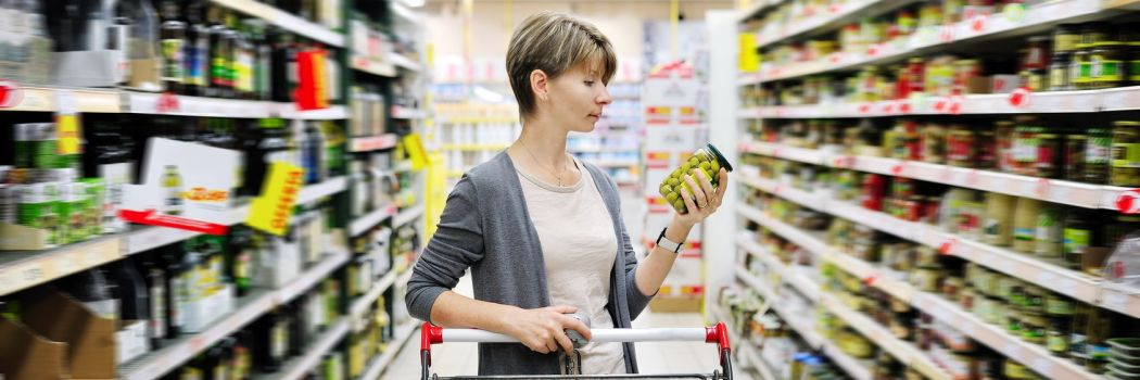woman with a cart shopping looking at a nutrition label at the supermarket