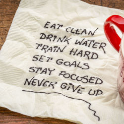 Notes about goals for better health written on a napkin next to a mug of coffee