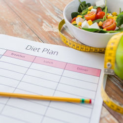 Empty diet plan next to measuring tape, salad, and an apple
