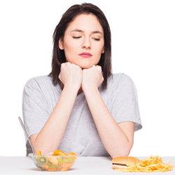 a woman debating between unhealthy food and a salad
