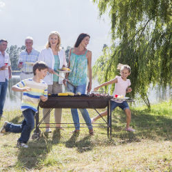family having a barbecue together at a lake