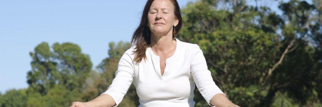 Woman meditating in an open green field
