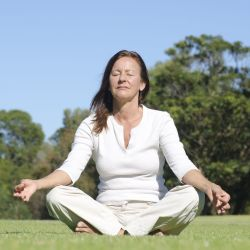 Woman meditating in an open green field
