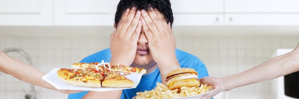 Young man covering his eyes to unhealthy food