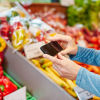 Woman using her phone to help her shop in the produce aisle