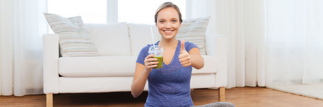 Woman on a yoga mat holding a green smoothie giving a thumbs up