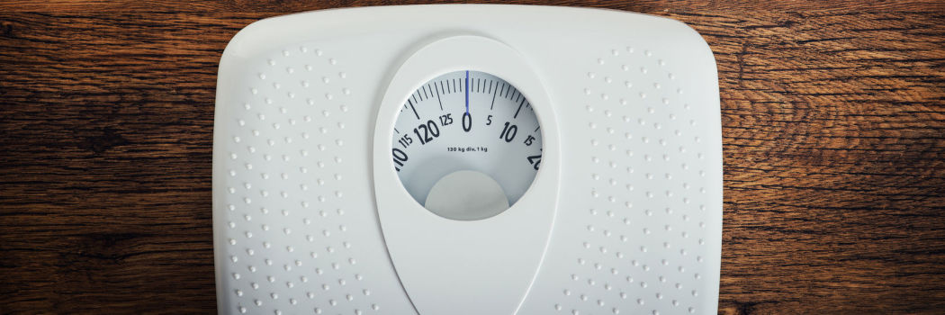 Weight loss concept with a scale on a wood floor
