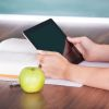 close up of a woman with an apple reading something on a tablet
