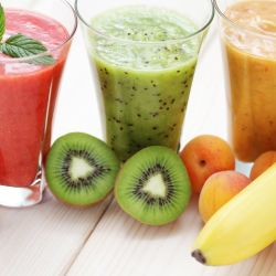 A strawberry smoothie, kiwi smoothie, and banana smoothie displayed on a table with fruit ingredients in front of the smoothies