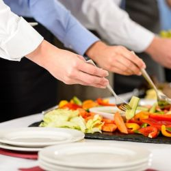 hands holding forks at a healthy buffet table