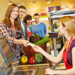 Smiling woman paying at the supermarket checkout
