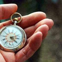 A woman's hand holding an old pocket watch