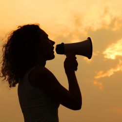 woman's silouette holding a megaphone making a proclamation in front of a sunset sky