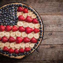 blueberries, strawberries, and bananas arranged in a pie to look like an american flag