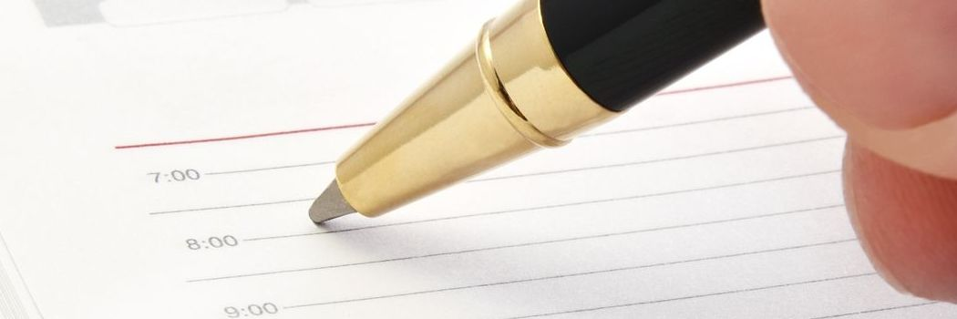 A hand poised with a pen getting ready to write in a schedule