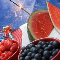 raspberries, blueberries, and watermelon on a table with noise makers and a sparkler for a 4th of July celebration