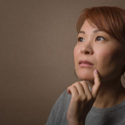 A middle aged woman staring off into the distance in deep thought