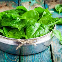 Fresh spinach in a bowl on wooden rustic table