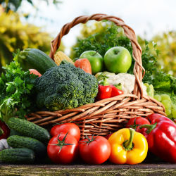 an overflowing basket of colorful vegetables and fruit on a wooden table outside
