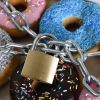 box full of delicious donuts wrapped in metal chain and lock as a commitment device to stop food addiction and stay on your diet