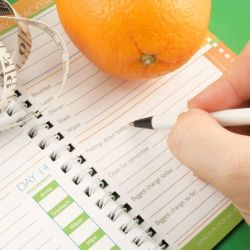 an orange and measuring tape on a journal for weight loss